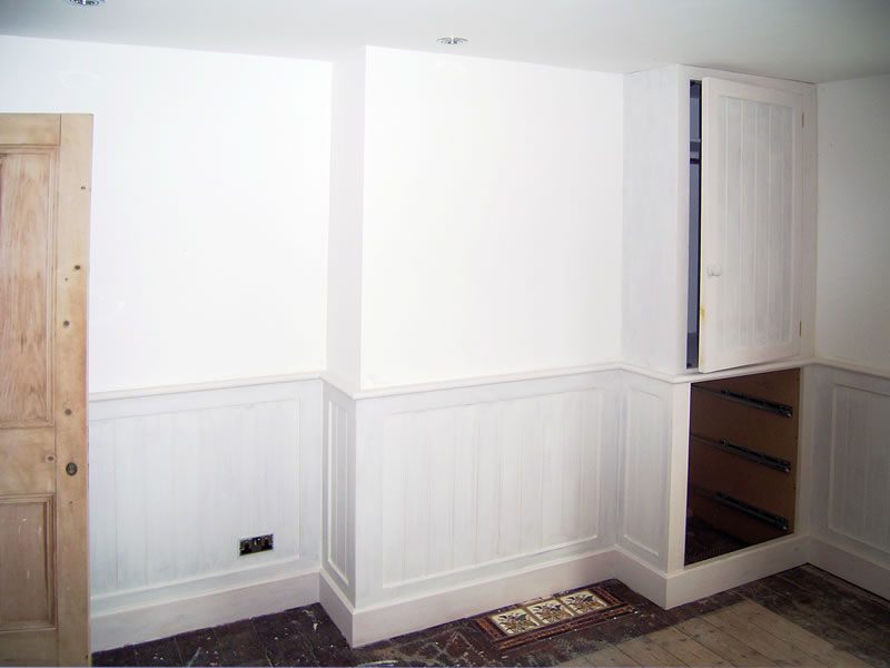 MDF T and G dado panelling and cupboard including drawer fronts split to match panelling