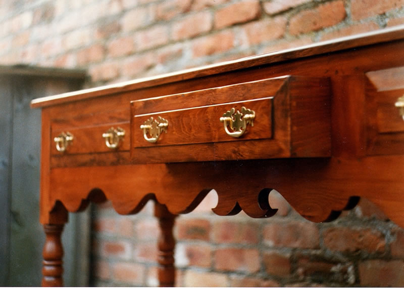 yew-dresser-base-with-shaped-bottom-rail-showing-hand-cut-dovetails-on-drawers