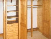 Pine wardrobe with raised and fielded panels showing internal hanging space shelf storage and drawers