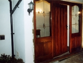 Door and frame designed to match early style plank doors with a baton nailed-over-joints-curved-tops-of-the-panelled-side-lights-to-soften-the-otherwise-square-appearance