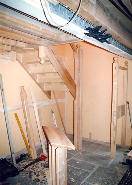 Yellow pine staircase newel posts and landing section being assembled